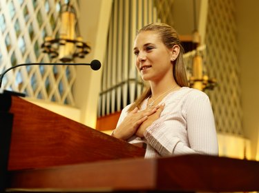 Teenage girl (16-17) in church standing at lectern, low angle