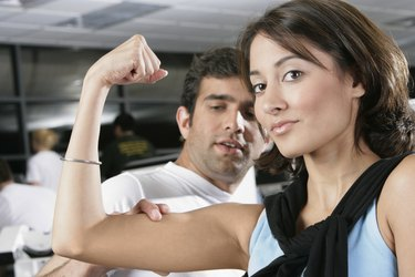 Portrait of a young man measuring a young woman's bicep