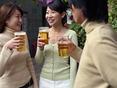 Two young women and young man holding pints of beer outside pub