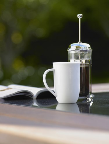 Coffee cup and plunger on table
