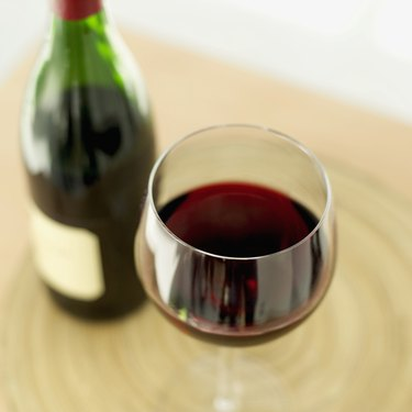 close-up of a glass of red wine with a wine bottle on a table