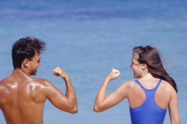 Couple flexing muscles by sea, rear view