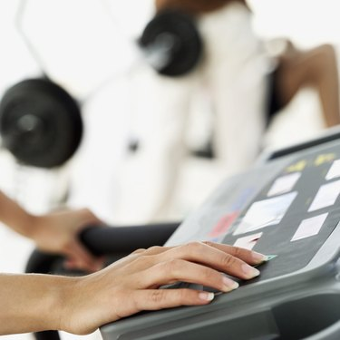 close-up of the hand of a woman selecting an exercise program on a treadmill