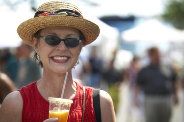 Close-up of a mature woman holding a glass of orange juice and smiling