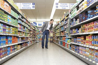 Man with basket shopping in supermarket, looking at items on shelf