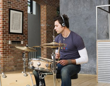 Man playing drums while wearing headphones