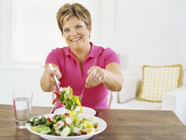 mature woman serving salad with a fork
