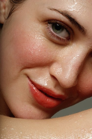 Young woman perspiring, smiling, portrait, close-up