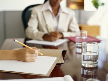 Businesspeople writing on conference table, focus on woman's hand in foreground