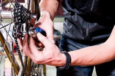 Close-up of man fixing bicycle