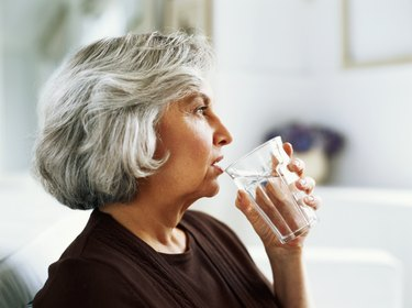 Senior woman drinking water, close-up, side view
