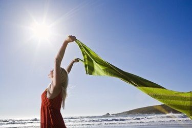 Woman with fabric fluttering on beach