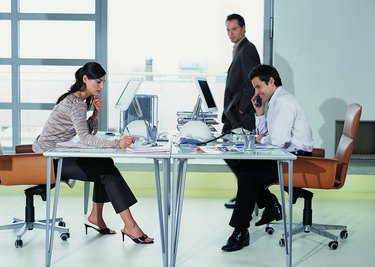 Two Business Colleagues Working Face to Face at Their Desks With Another Businessman Walking Past in the Office