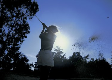 low angle view of a female golfer swinging her golf club