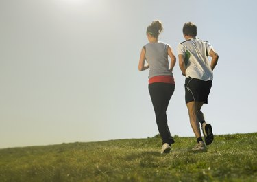 Man and woman jogging on grass, rear view