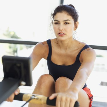 close-up of a young woman exercising on a rowing machine