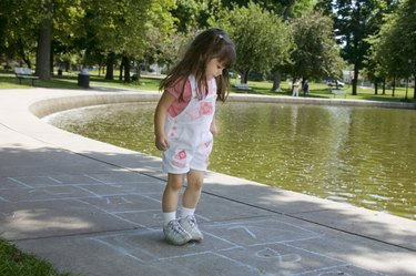 Girl playing hopscotch by pond