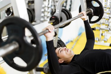 Young handsome man doing exercises on a bench press