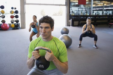 Serious exercise class doing kettlebell squats at gym