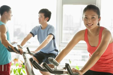 Young people on stationary bikes exercising in the gym