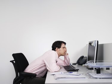 Bored Male Office Worker At Desk