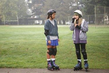 Teenage girls (13-14) wearing in-line skates in park