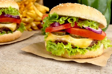 Big cheeseburgers with french fries on wooden desk