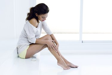 Body care. Woman applying cream on legs