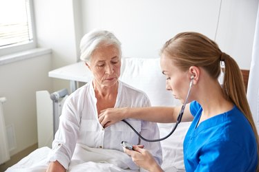 nurse with stethoscope and senior woman at clinic