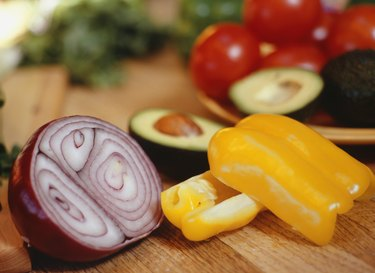 Sliced onion, peppers and avocado on table, close-up