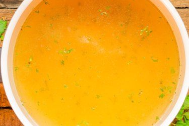 Closeup of broth, clear soup or bouillon  in a saucepan