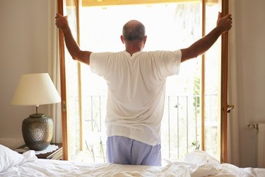 Rear View Of Man Waking Up In Bed In Morning