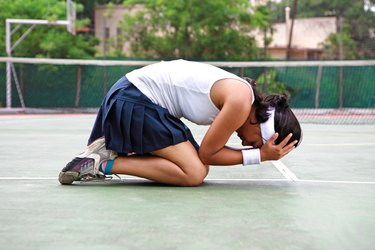 Young woman kneeling on a tennis court