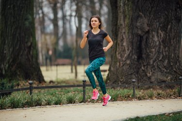 Young girl running outdoors in a city park
