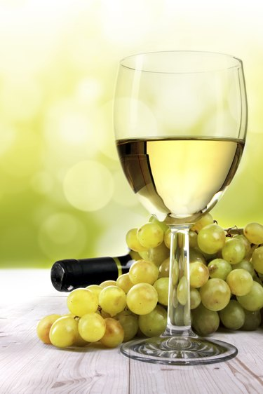 White wine glass, grapes and bottle on table in vineyard