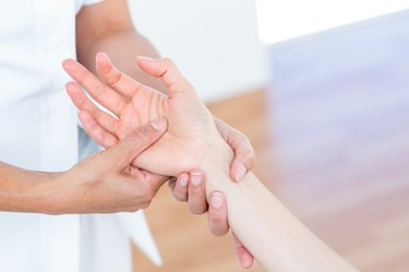 Physiotherapist massaging her patients hand