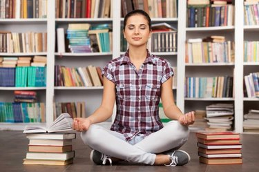 Beautiful young woman keeping her eyes closed and meditating while sitting at the library