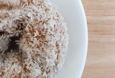 Top close view of coconut flake donut on white plate