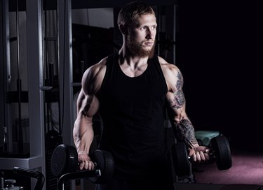 athletic guy bodybuilder , execute exercise with dumbbells, in dark gym