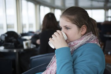 Young Teenage Girl Drinking From Paper Cup On a Ferry