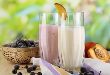 Delicious milk shakes with blackberry and peach on wooden table