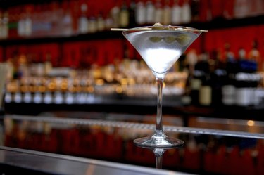 Dirty Martini on Bar with Bottles in Background