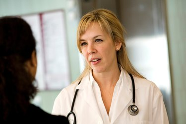 Female doctor talking to patient in hospital.