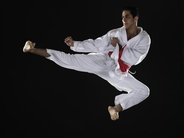 Young man practicing martial arts, jumping in midair
