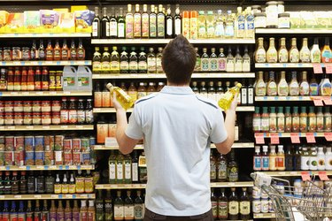 Young man looking at bottles of oil in market, rear view, close-up