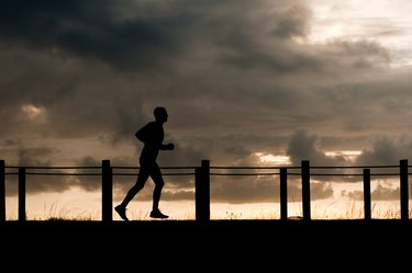 silhouette of an athlete running under a stormy sky
