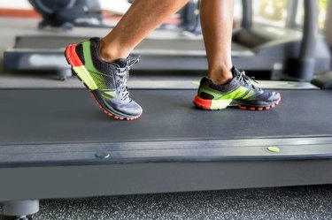 Close up man running on treadmill in the gym