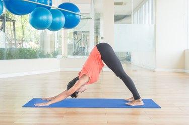 Asian woman make yoga Downward facing dog pose in classroom
