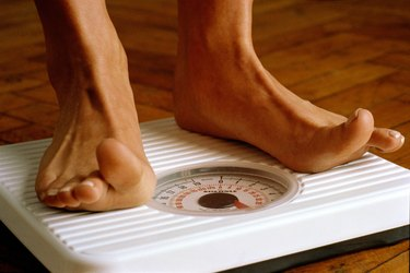 Woman weighing herself on bathroom scales,detail of feet