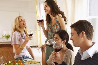 Three young women and young man drinking red wine, two women laughing
